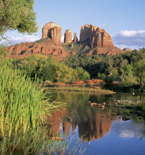 A blue lake and green vegetation sits at the base of the red rock formation: Cathedral Rock