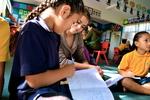 Student writing stories in Maori